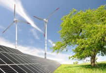 Spring landscape with solar energy panels and wind turbine