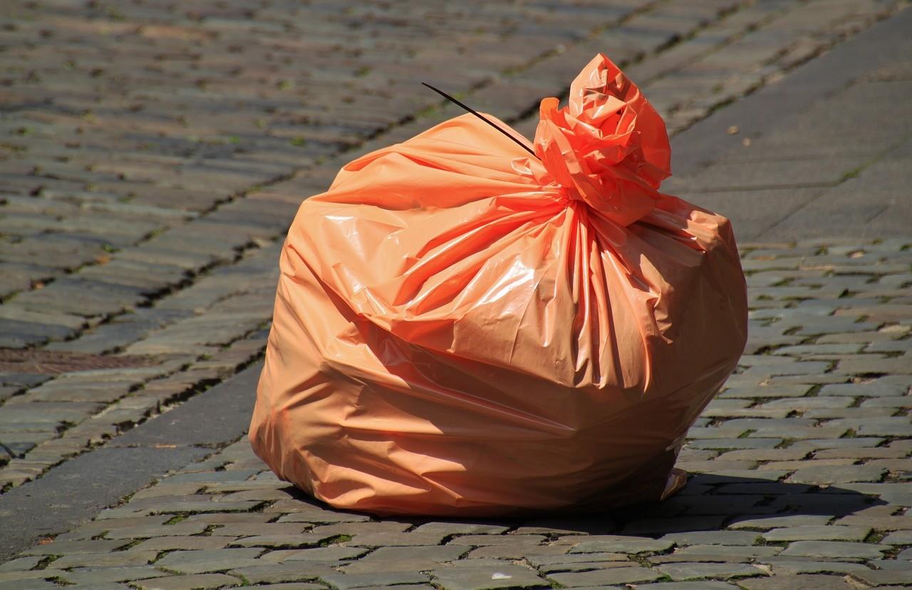 Pomarańczowa torba na śmieci na ulicy