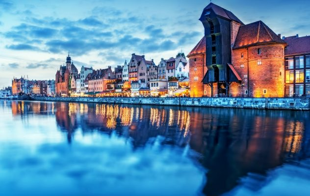 Gdansk old town and famous crane, Polish Zuraw. View from Motlawa river, Poland at romantic sunset, night. The city also known as Danzig and the city of amber.