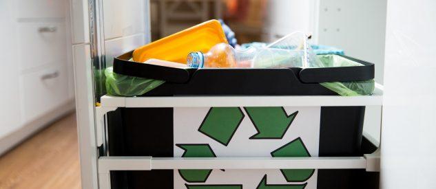 Kosz na selektywną zbiórkę odpadów ze znakiem recyklingu i plastikową butelką w środku