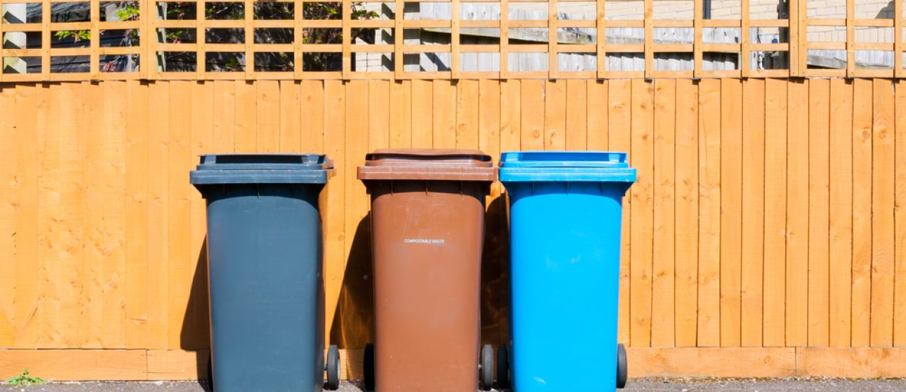 Three plastic waste bins outside a house along the fence