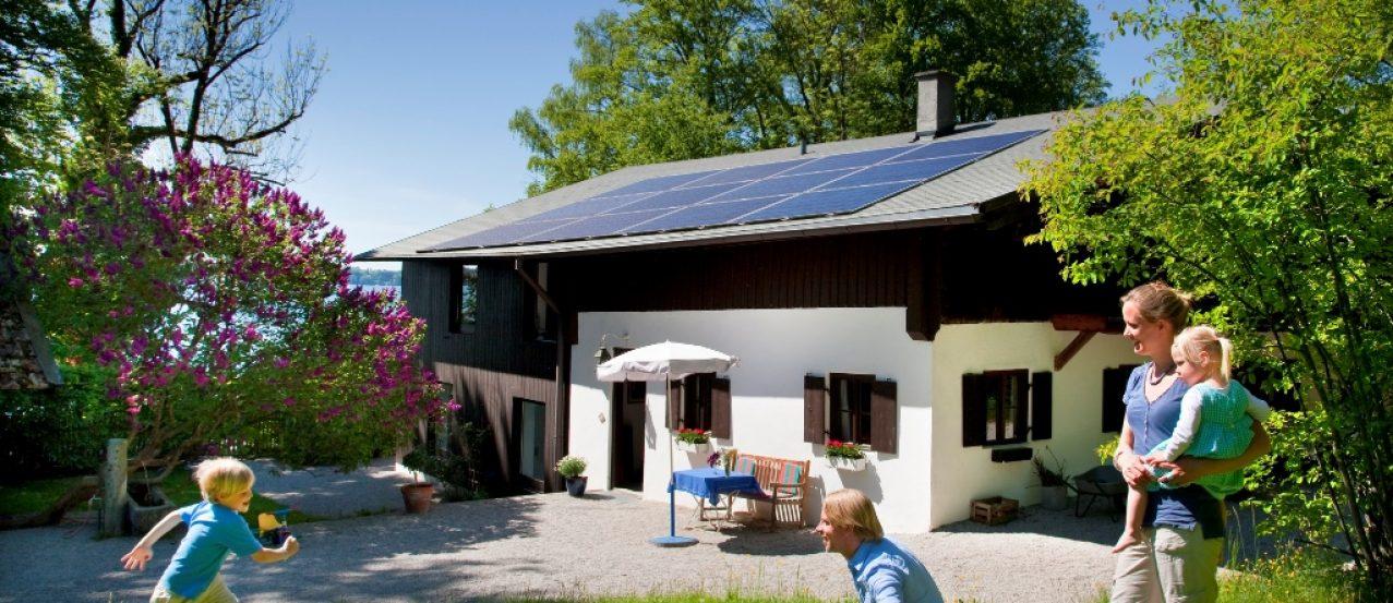 Rodzina przed domem wyposażonym w panele fotowoltaiczne IKEA zamontowane na dachu