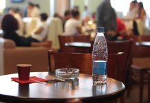 Kawiarniany stolik na lotnisku z butelką wody i kubkiem kawy