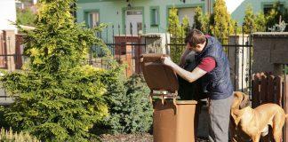 Mężczyzna wyrzucający odpady do brązowego pojemnika