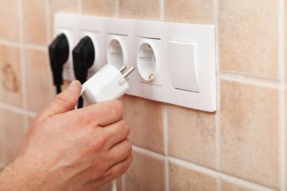 Dłoń podłączająca przewód do gniazdka elektrycznego