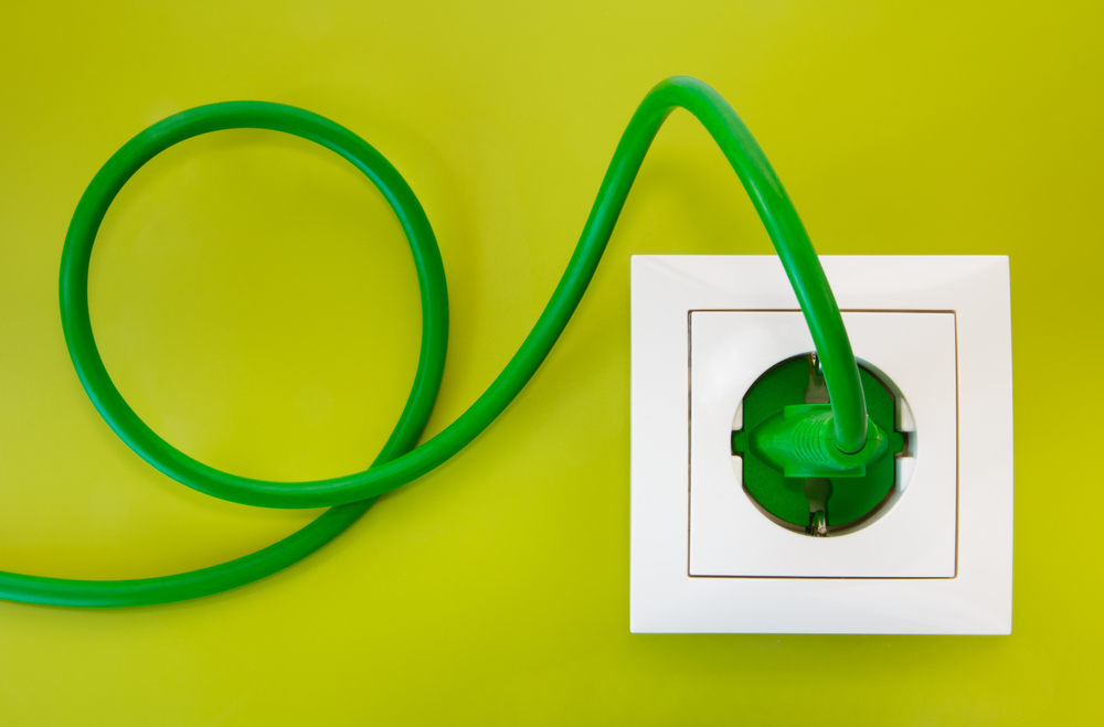 Green power plug into white power outlet against a olive green background