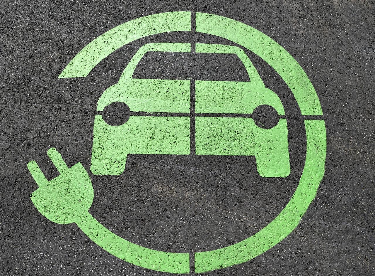Zielony symbol ładowania samochodów elektrycznych na parkingu