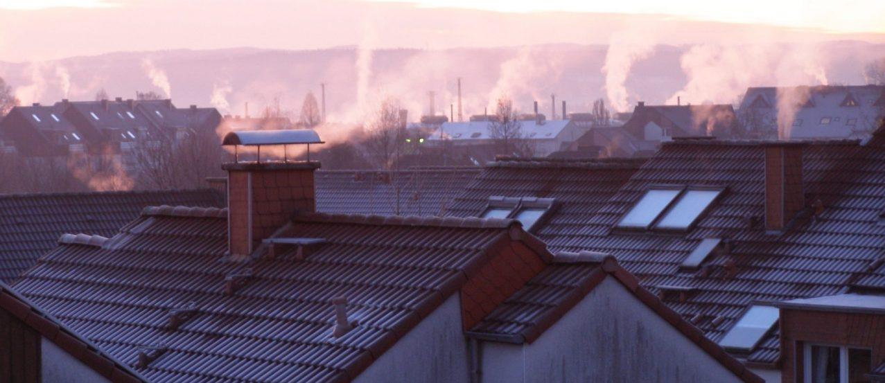 Kominy i dachy ze smogiem w tle