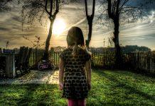 Dziewczynka stojąca przed płotem na wsi