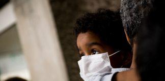 Dziecko w masce antysmogowej trzymane na rękach przez dorosłego