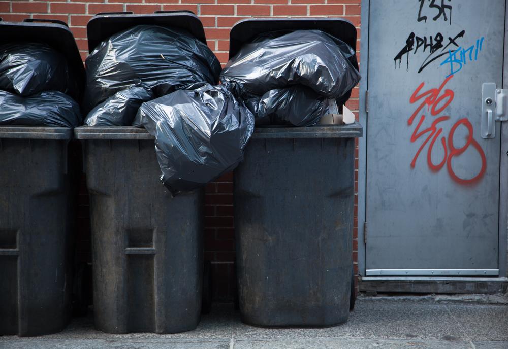 Czarne pojemniki na śmieci (odpady) z wystającymi workami na tle ceglanego muru