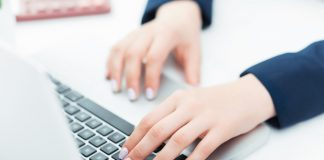The hands of woman on the keyboard of her laptop computer