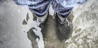 Człowiek stojący w wodzie podczas powodzi ubrany w kalosze