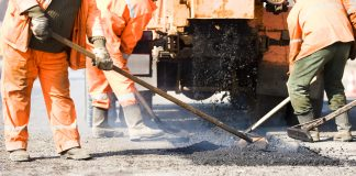builders at Asphalting paver machine during Road street repairing works
