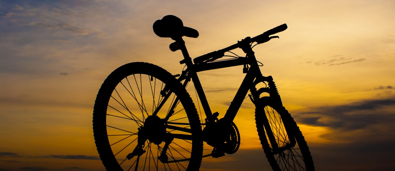 Silhouette of mountain bike parking on jetty beside sea with sunset sky background