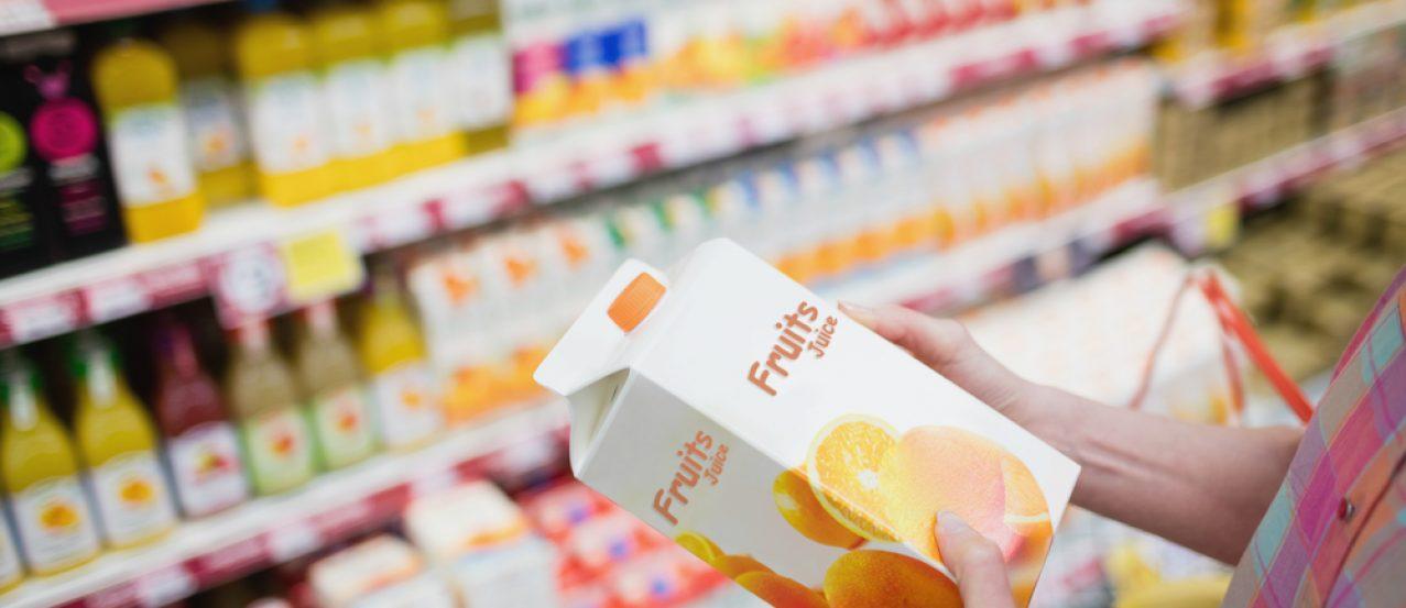 Zbliżenie na dłonie kobiety w sklepie trzymające sok pomarańczowy w kartonie