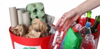 Putting empty bottles into recycling bins, closeup